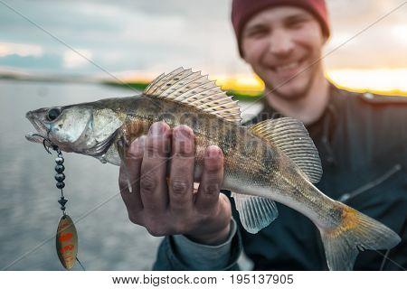 Happy fisherman holds the fish
