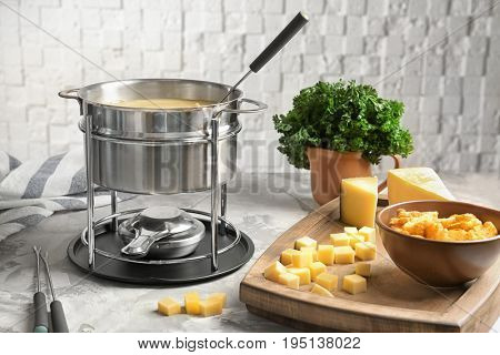 Delicious cheese fondue with rusks on table