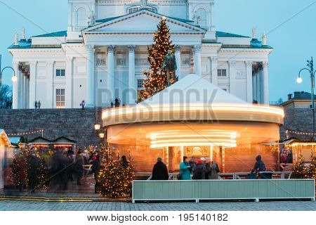 Helsinki, Finland. Xmas Market On Senate Square With Holiday Carousel And Famous Landmark Is Lutheran Cathedral And Monument To Russian Emperor Alexander II At Winter Evening