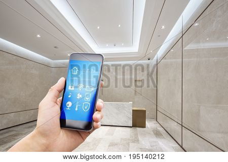 mobile phone with app on smart home in reception desk of modern office building