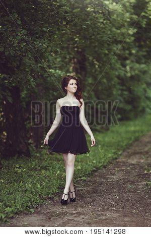 Beautiful young brunette girl in short black dress walking in the park. Little black dress.