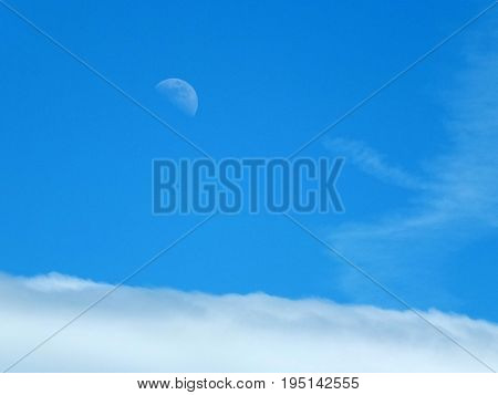 pale daytime moon in blue summer sky above the clouds