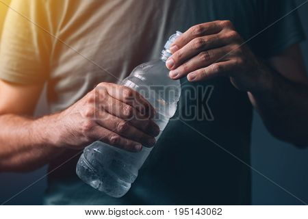 Man with bottle of fresh drinking water for refreshment and rehydratation