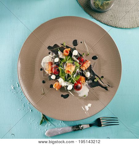Restaurant Salad Food - Black Caesar Salad with Smoked Salmon. Gourmet Restaurant Salad Menu. Salad Garnished with Rucola, Green Leaves and Vegetables