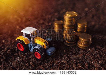 Agricultural tractor toy and golden coins on fertile soil land income from activity in agriculture or investment and bank loans for farm development