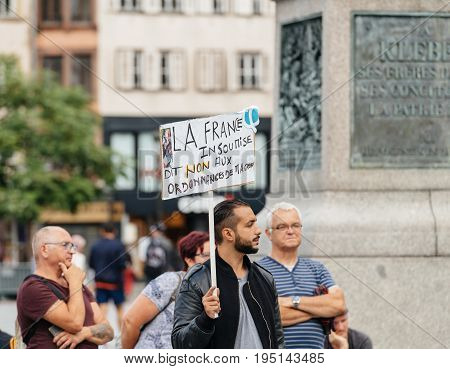 STRASBOURG FRANCE - JUL 12 2017: Protesters with placards at protest against Macron government spending cuts and pro-business tax and labor reforms