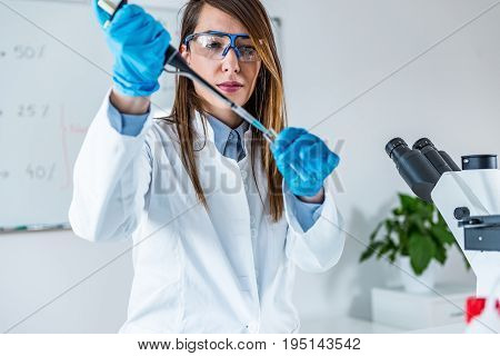 Laboratory Technician With Micro Pipette, One Woman Only, Toned Image