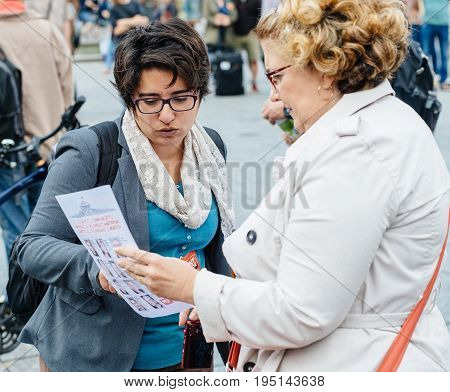 STRASBOURG FRANCE - JUL 12 2017: Senior woman debating at protest against Macron government spending cuts and pro-business tax and labor reforms