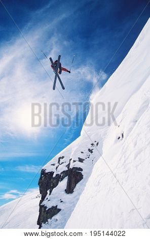 Low angle view of freestyle skier jumping from mountain ledge