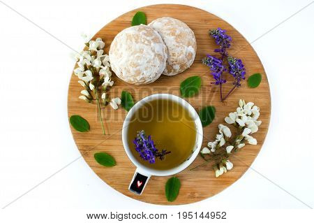 A Cup Of Herbal Tea And A Honey Cookies Covered With White Sugar Glaze On A Wooden Sand Board. Flowe
