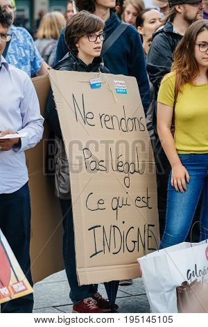 STRASBOURG FRANCE - JUL 12 2017: Woman waring placard in city as Melenchon called for day of protest against Macron government spending cuts and pro-business tax and labor reforms