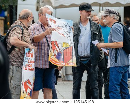 STRASBOURG FRANCE - JUL 12 2017: Man showing placard to protesters in city as Melenchon called for day of protest against Macron government spending cuts and pro-business tax and labor reforms