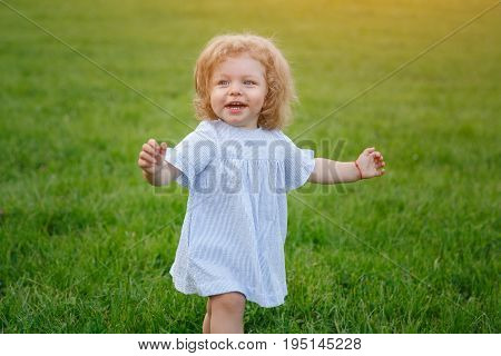 Portrait of young blonde girl looking away smiling walking on grass.