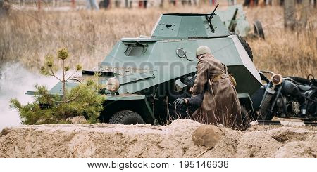 Gomel, Belarus - November 26, 2016: Re-enactor Dressed As Red Army Russian Soviet Infantry Soldier Of World War II Rescues Driver Crew From A Destroyed Armoured Soviet Scout Car At Battlefield During Historical Reenactment.