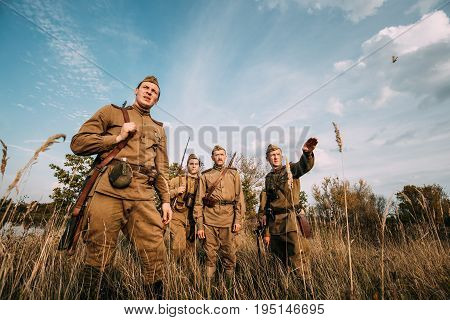 Dyatlovichi, Belarus - October 1, 2016: Re-enactor Dressed As Russian Soviet Infantry Soldier Of World War II Specifies Hand Forward To His Soldiers In Autumn Field During At Historical Reenactment