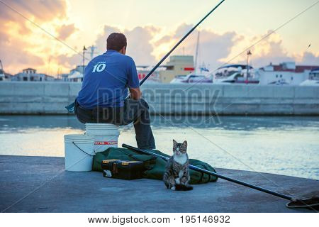 CYPRUS LIMASSOL - SEPTEMBER 22 2016: Local with cat fishing in the Limassol Old Port at sunset.