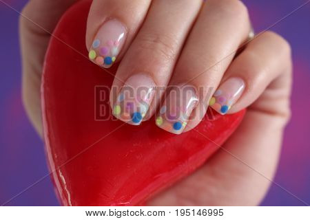 Spotted cheerful nails/ Spotted nails and red heart in palm.