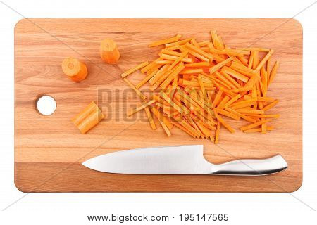 Coarsely chopped carrots and chef's knife on wooden cutting board close-up top view