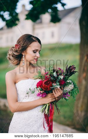 Bright wedding bouquet in bride's hand outdoor