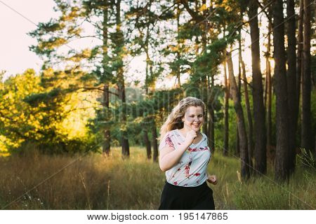 Young Pretty Plus Size Caucasian Happy Smiling Laughing Girl Woman In White T-Shirt, Running In Summer Green Forest. Fun Enjoy Outdoor Summer Nature.