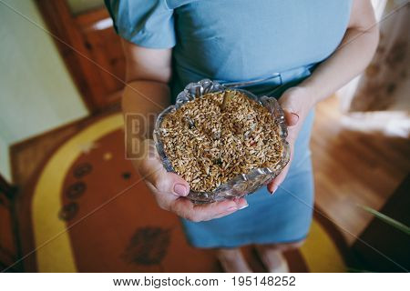 A woman holding a dish with wheat
