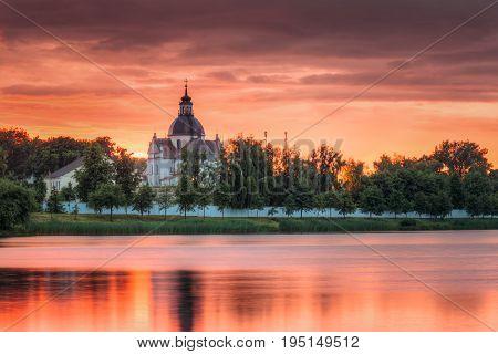 Nesvizh, Minsk Region, Belarus. Corpus Christi Church And Castle Pond Lake At Summer Sunset Evening Or Sunrise Morning. Famous Landmark In Nyasvizh.