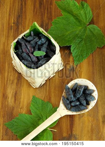 Honeysuckles in a wicker basket and in a wooden spoon on a wooden background