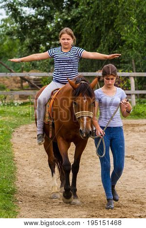 Vynohradiv Ukraine - July 12 2017: Girls learn horseback riding during a vacation in the summer children's equestrian sports camp.