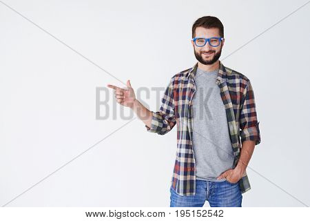 Close-up shot of man wearing casual clothes pointing sideway at cope space. Young bearded man wearing blue glasses