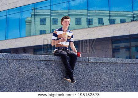 Low angel of student in headphones having lunch while sitting on stone wall Drinking coffee. Wearing casual clothes and straw hat