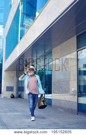 Vertical of fashionable old man talking on phone and walking down street while carrying handbag