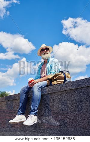 Vertical of relaxed guy aged of 50-60 enjoying city while drinking coffee and sitting on bordure