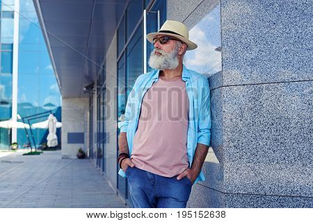 Elderly man wearing sunglasses, jeans and T-shirt holding hands in pockets, leaning on wall, mid shot