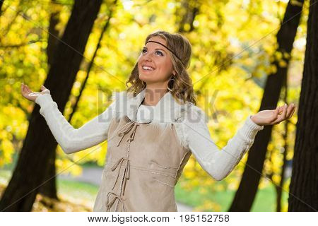 Beautiful boho girl enjoys in the park with her arms outstretched.