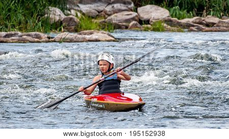 Village Myhia Mykolayiv region South Bug River Ukraine - July 9 2017: A teenager trains in the art of kayaking. Boat boats on rough river rapids. The child is skillfully engaged in rafting.
