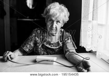 Elderly woman pensioner measures the blood pressure itself. Black-and-white photo.