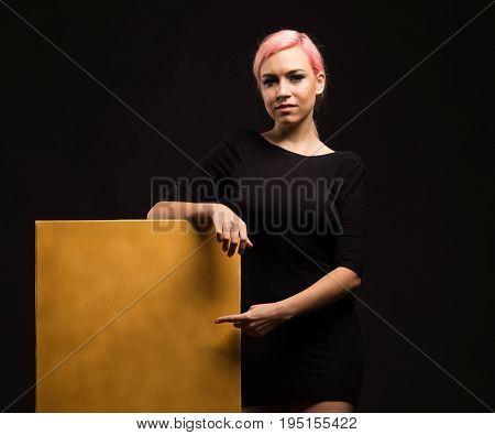 Young glad woman portrait of a confident businesswoman showing presentation, pointing gold placard, black background. Ideal for banners, registration forms, presentation, landings, presenting concept.