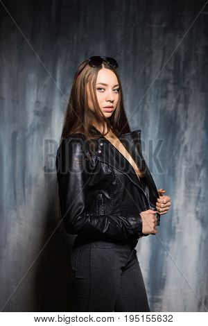 Portrait of sexy young woman posing in black jacket and jeans