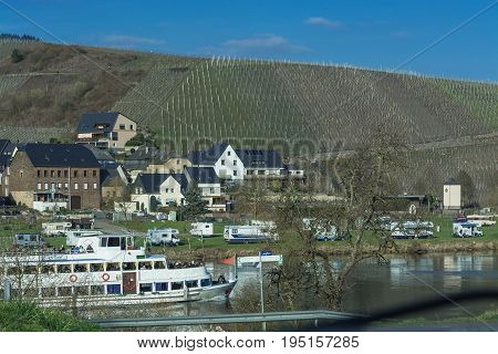 TRABEN-TRARBACH GERMANY - MARCH 26 2016: Passenger ship MS Berlin on the Moselle near the town of Traben-Trarbach in Germany. In the background mobile home on a campsite