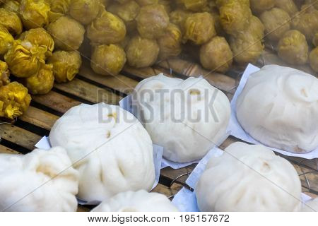 Chinese steamed dumpling being steamed on the traditional bamboo pan