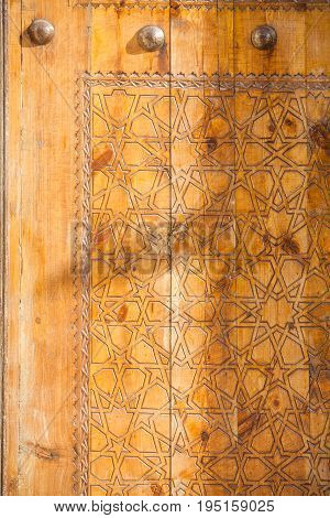 Arabic decorations close up on a wooden door.