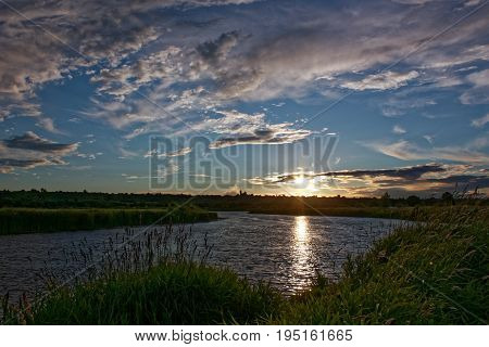 Beautiful shades and clouds in the sky are reflected in the river surface at the time of sunset.