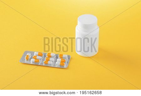 Pharmaceutical medicine pills, tablets and capsules on a yellow background. Pills, tablets, vitamins, medicine, and drugs. White bottle near the blister.