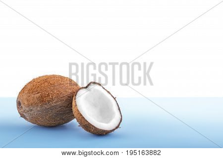 Beautiful coconuts isolated on a white background. Delicious coco on a bright light blue background. Fresh nutritious coconut cut in half. Healthful vegetarian diet