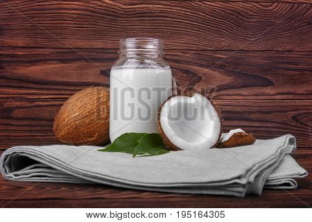 Coconuts and a jar of coconut milk on a gray piece of cloth on a dark wooden background.  Cut tasty coconuts and a bottle full of delicious fresh milk. Beautiful nutritious nuts.