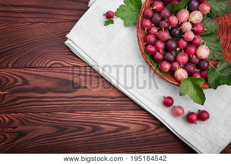 Tasty, juicy, healthy, ripe multi-colored gooseberries with green leaves in a light brown basket on a dark brown wooden table.  Juicy, raw, fresh, tasty, healthy, nutritious concept.