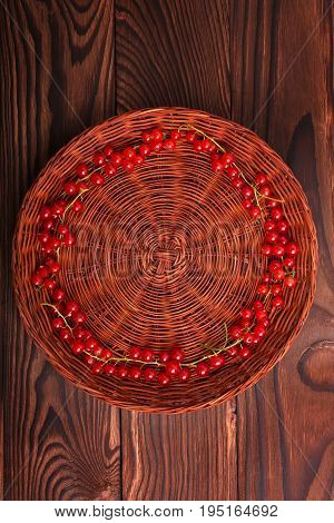 A brown wooden crate with tasty and ripe currant on a dark brown background.  Mature, healthy, nutritious and ripe currant are lying inside, forming a circle. Delicious bright red currant.