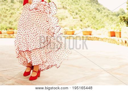 Low section of female flamenco dancer dancing outdoors