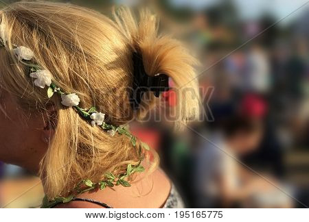 Blond woman wearing a flower crown with white fowers and green leaves at a festival with a blurred background and space for text.
