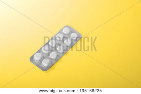 A shiny pack of antibiotics on a bright yellow and brilliant background.  Close-up  white prescripted drugs. Painkillers,  tablets, medications, vitamins in a small package.